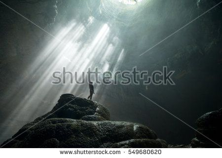 Girl stands under the ray of light in the cave. Jomblang cave. Java, Indonesia