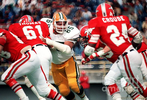 Photograph of Edmonton Eskimos defensive lineman Dave Fennell #65 keys in on this play against the Calgary Stampeders, Labour Day 1983.