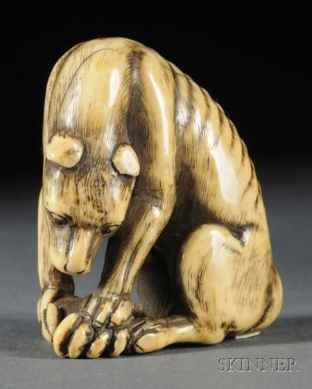 Ivory Netsuke, 18th century, study of a wolf with a crab, ht. 2 in.