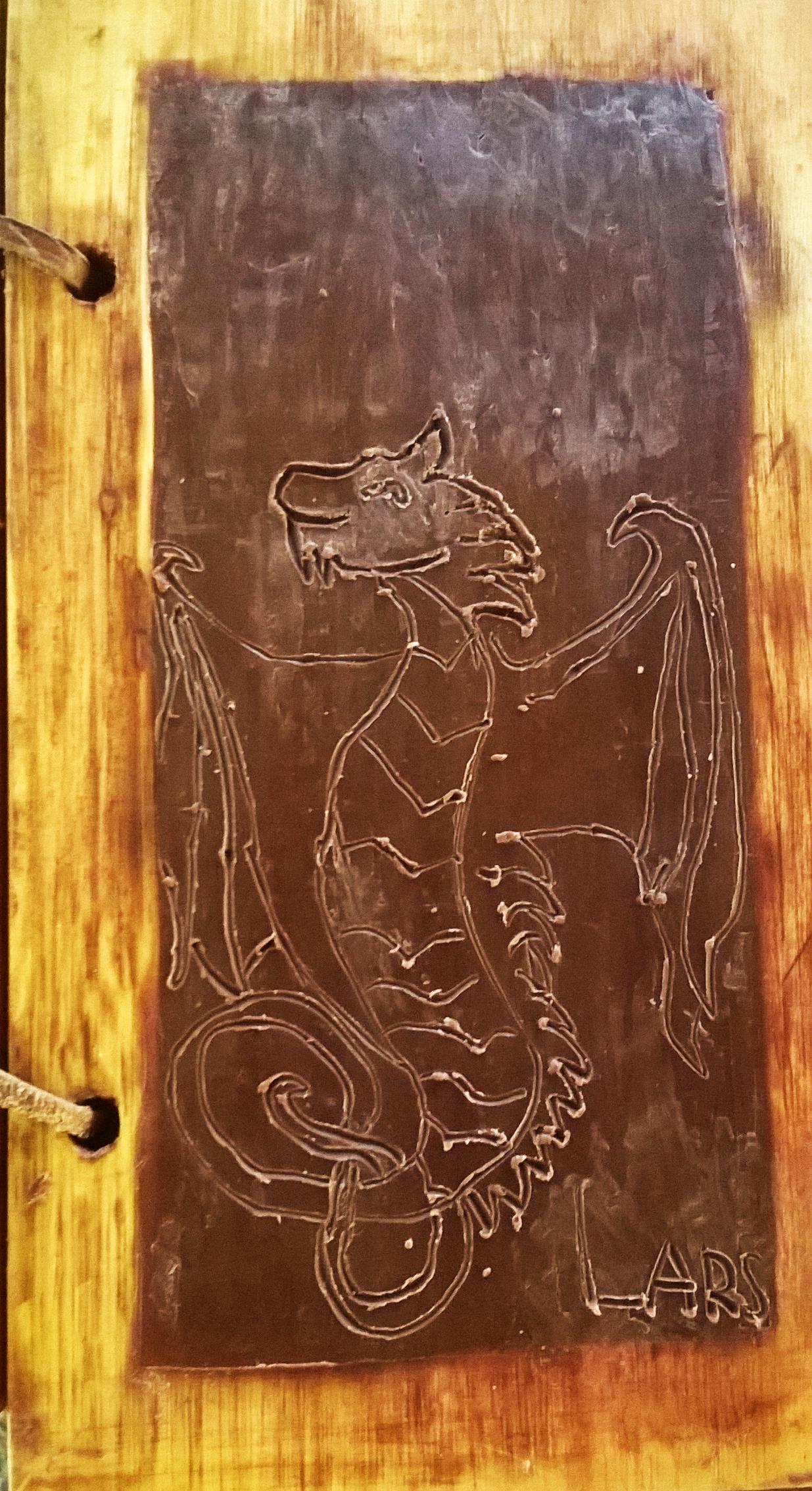 Art et cire, voici séant un dragon dessiné au stylet sur tablette de cire par un jeune garçon. Du talent sans aucun doute.