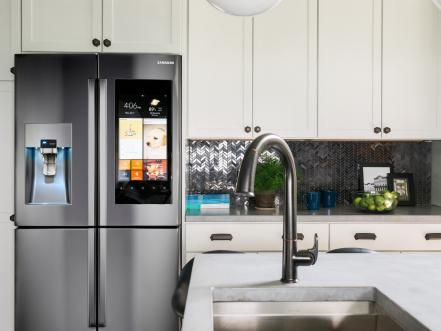 In the kitchen, state-of-the-art technology lives peacefully with classic black-and-white style. A shimmery geometric backsplash lends a little glam to white cabinetry and concrete countertops, while innovative (and great-looking) appliances make the space top-of-class smart.