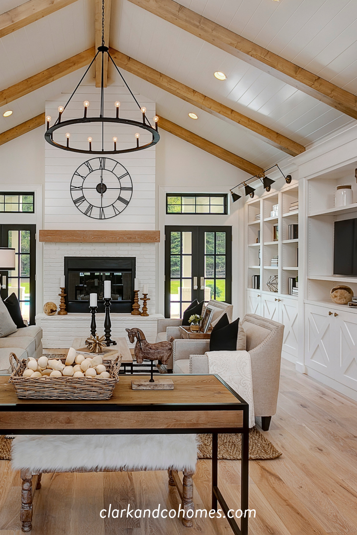 The Warm Natural Wood Of The Flooring Ties Into The Vaulted Ceiling Beams And The Firep Vaulted Ceiling Living Room Beams Living Room Ceiling Beams Living Room