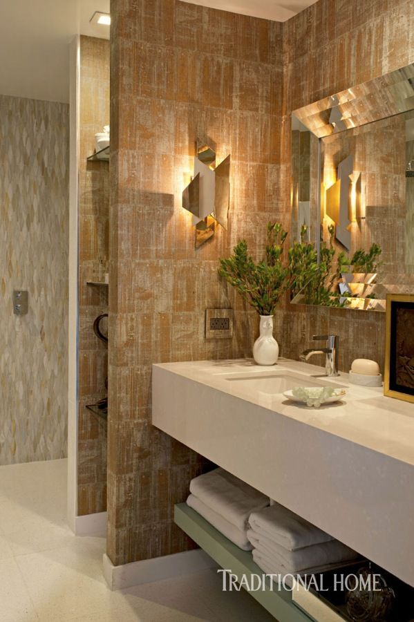 A gilded-cork wallcovering dresses the bathroom walls, which are illuminated by brass sconces. - Photo: Michael Garland / Design: Keith Fortner