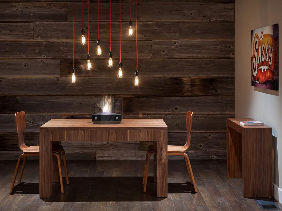 To give your dining room an instant update on a budget, simply hang exposed Edison light bulbs from red wire. The stylish lighting option balances the rustic wood furniture. A modern tabletop fireplace is an unexpected centerpiece.