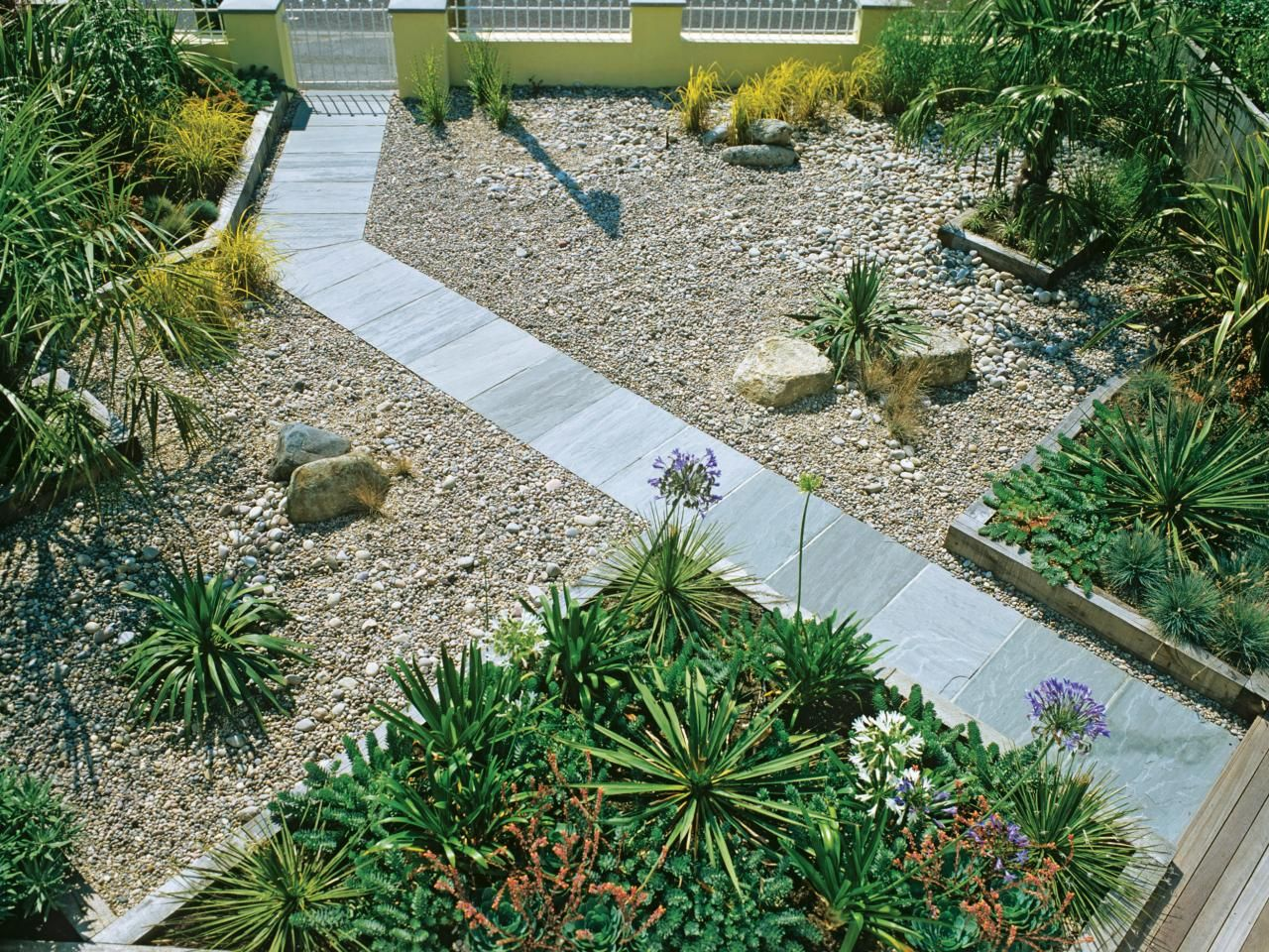 A slate path bisects a gravel yard with a garden that is divided ...