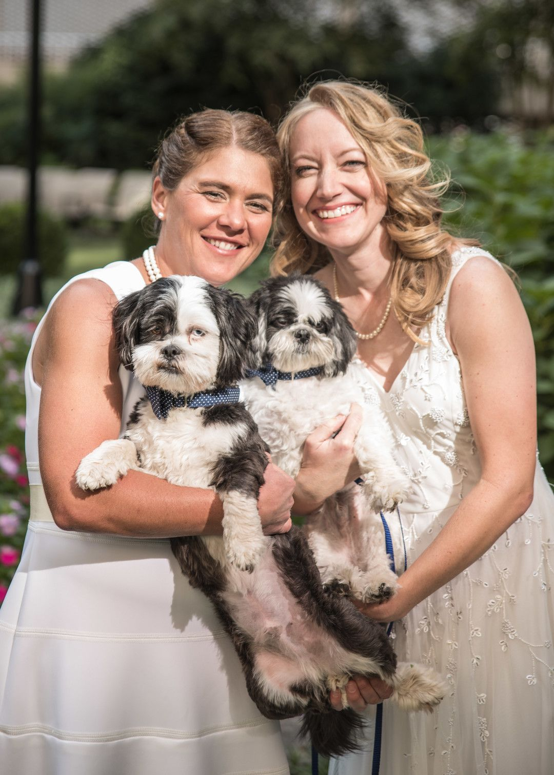 This couple had to move their wedding plans to evacuate a hurricane two  brides classic white dresses small dogs outdoor home wedding