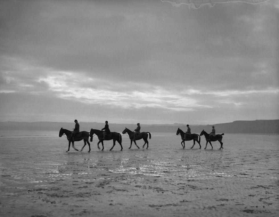 IlPost - Cavalcata sulla spiaggia - Un gruppo di allievi della scuola di equitazione Filey, nello Yorkshire, durante una cavalcata sulla spiaggia di Filey Sands, vicino a  Scarborough, nel Regno Unito. La foto è stata scattata il 2 febbraio 1934 (Fox Photos/Getty Images)