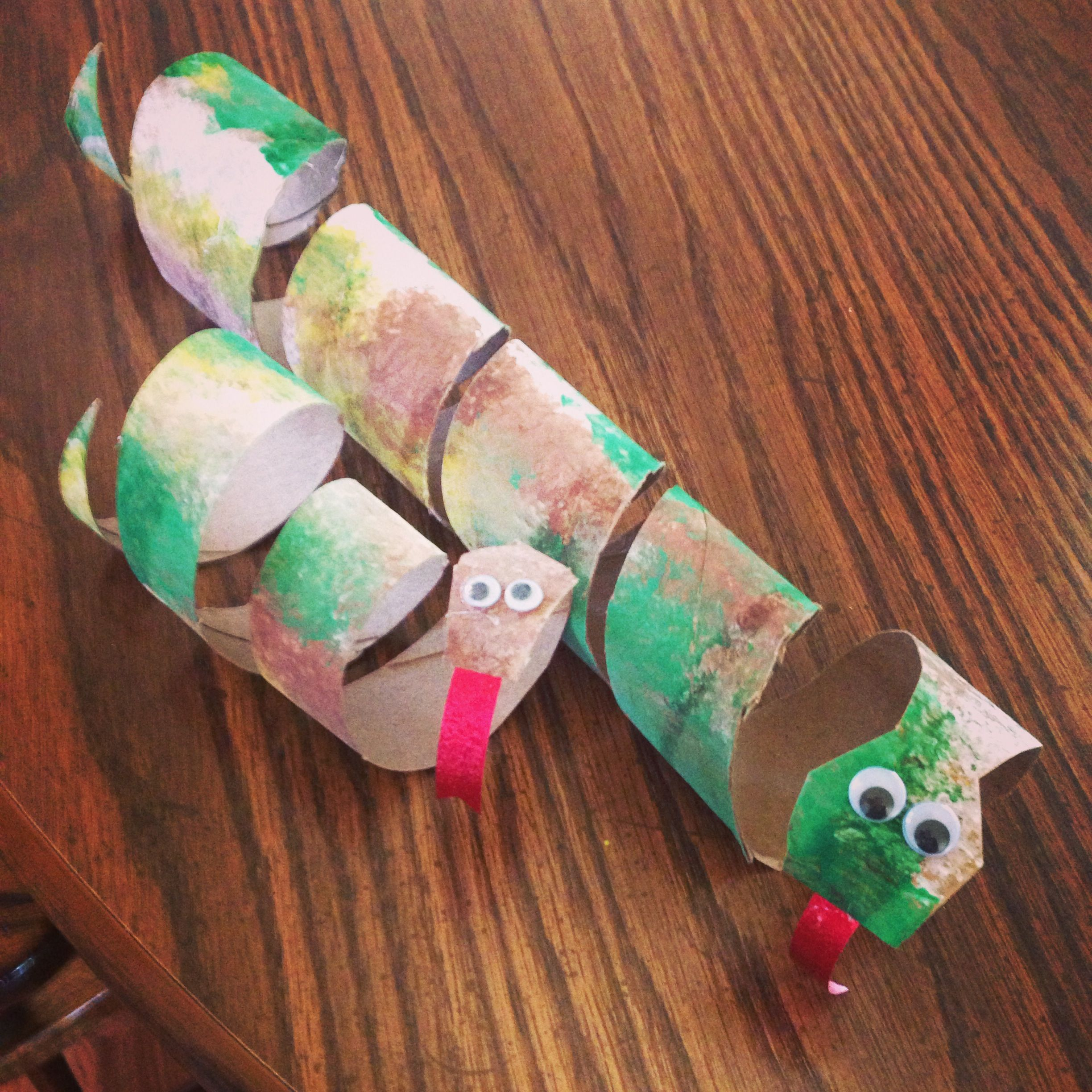 Paper towel roll for the mommy snake and toilet paper roll for the baby. We used sponges and fingerpaints, then cut, then hot glue a red ribbon tongue and beady eyes. Fun!