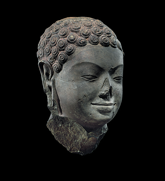 Head of Buddha, 7th century. The Metropolitan Museum of Art, New York. Gift of Doris Wiener, 2005 (2005.512) | This over-life-size head of the Buddha is a testament to the grandeur of the monumental sculptural tradition in the Zhenla kingdom. The Buddha has a strong, broad face; lightly modeled eyelids and pupils; and full lips that turn up at the corners in a hint of a smile. #LostKingdoms