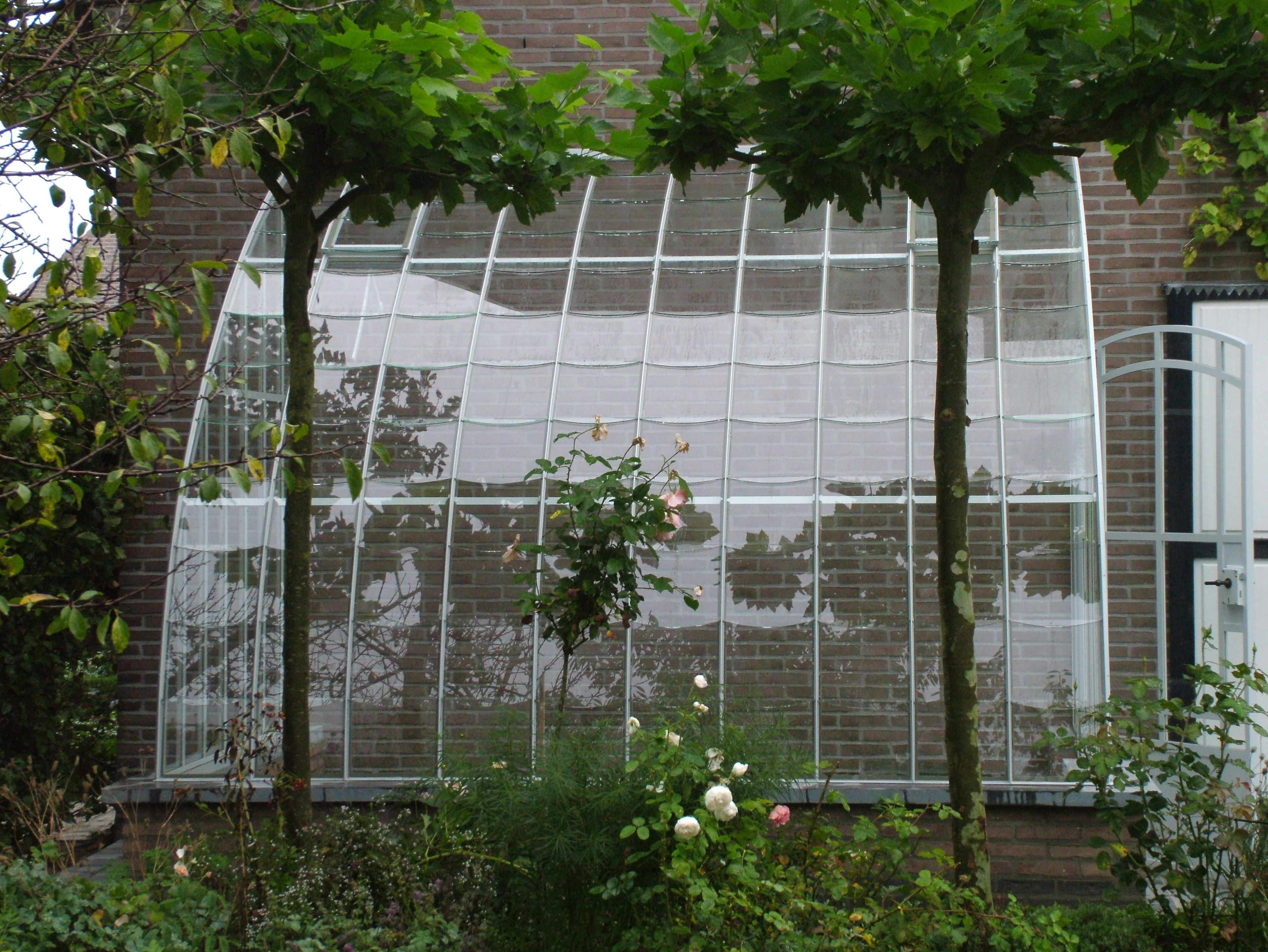 Serre En Fer Adossee Details De La Toiture Composee De Tuiles De Verre Mastiquees A L Ancienne Disposees En Ecailles Serre Jardin Jardins Serre