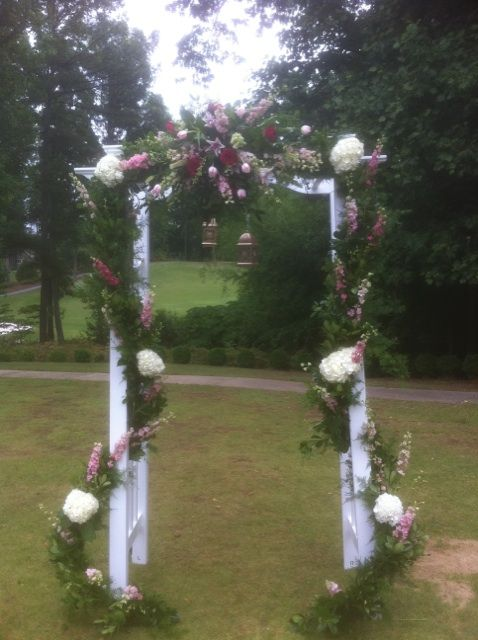 This Arch was decorated with a variety of greens Pink Larkspur and White Hydrangeas going down the sides. In the of the Arch we set a spray of flowers that include Stargazer lilies Pink tulips and Pink Larkspur. www.flowersfromus.net