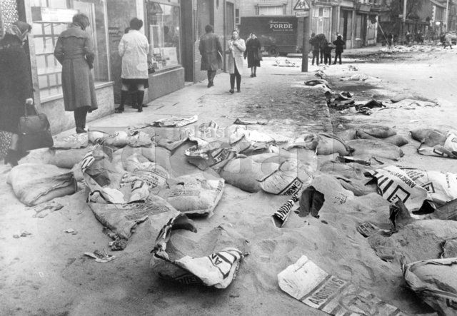 Riots : Belfast. February 1971. Morning shoppers climb over broken bags of meal scattered over the footpath on the Falls Road. They were thrown from a lorry hi-jacked during the rioting. (04/02/1971) | Belfast Telegraph Photosales