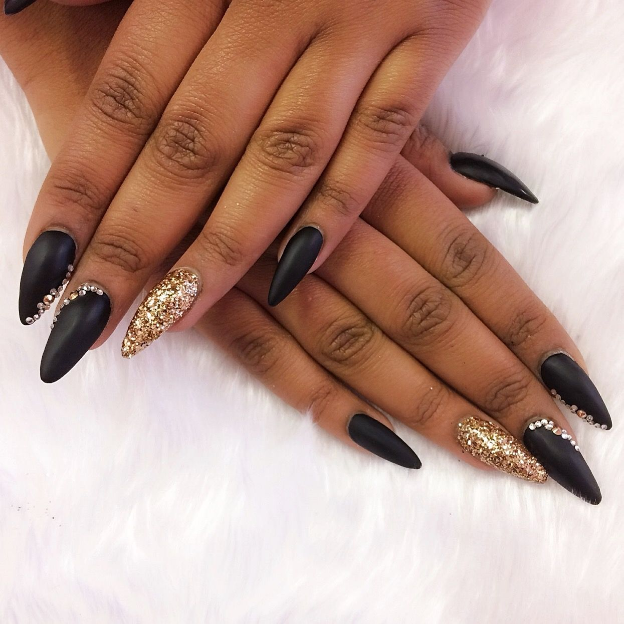 stiletto nails in matte black with gold glitter and