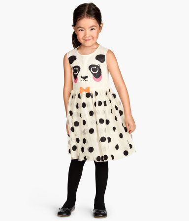 Sleeveless tulle dress with a glittery printed design. Seam at waist with decorative bow, flared skirt, and buttons at back. Lined.