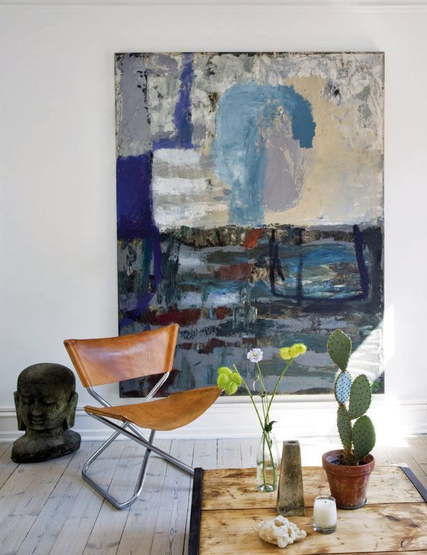 The home of designer Birgitte Rabens. Abstract canvas by artist Thaiwijit Puangkasemsomboon, Taiwan. Buddha (Bali) available at Rabens Saloner. Photo: Raúl Candales for Elle Decor España.