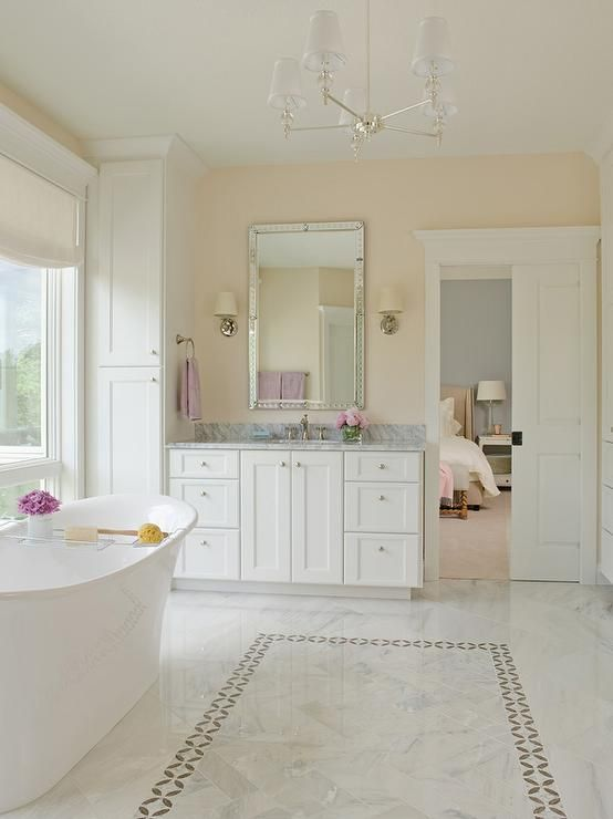 White And Cream Bathroom Features A Robert Abbey The Muses Chandelier  Illuminating A Freestanding Tub Placed Atop A Marble Herringbone Tiled  Floor Accented ...