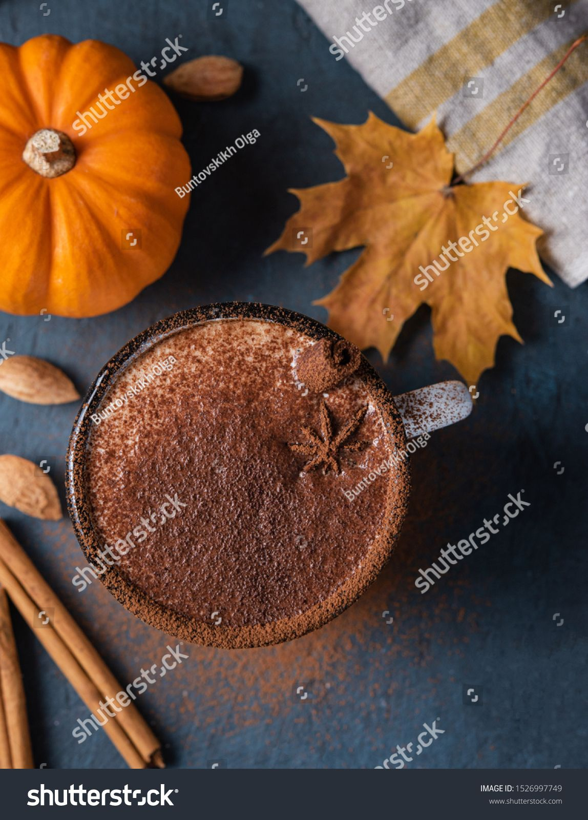 Aroma spice coffee latte drink with pumpkin milk foam cinammon and chocolate on the dark blue tableAutumn morning Image in vertical orientation