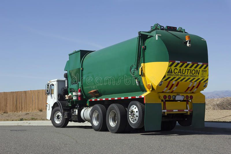 Garbage truck makes a turn on a street corner ad