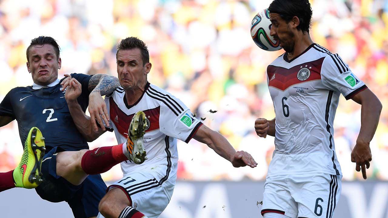Mathieu Debuchy despeja la pelota frente al delantero aleman Miroslav Klose y el mediocampista Sami Khedira durante el partido de cuartos de final. (AFP PHOTO / FRANK FIFE)