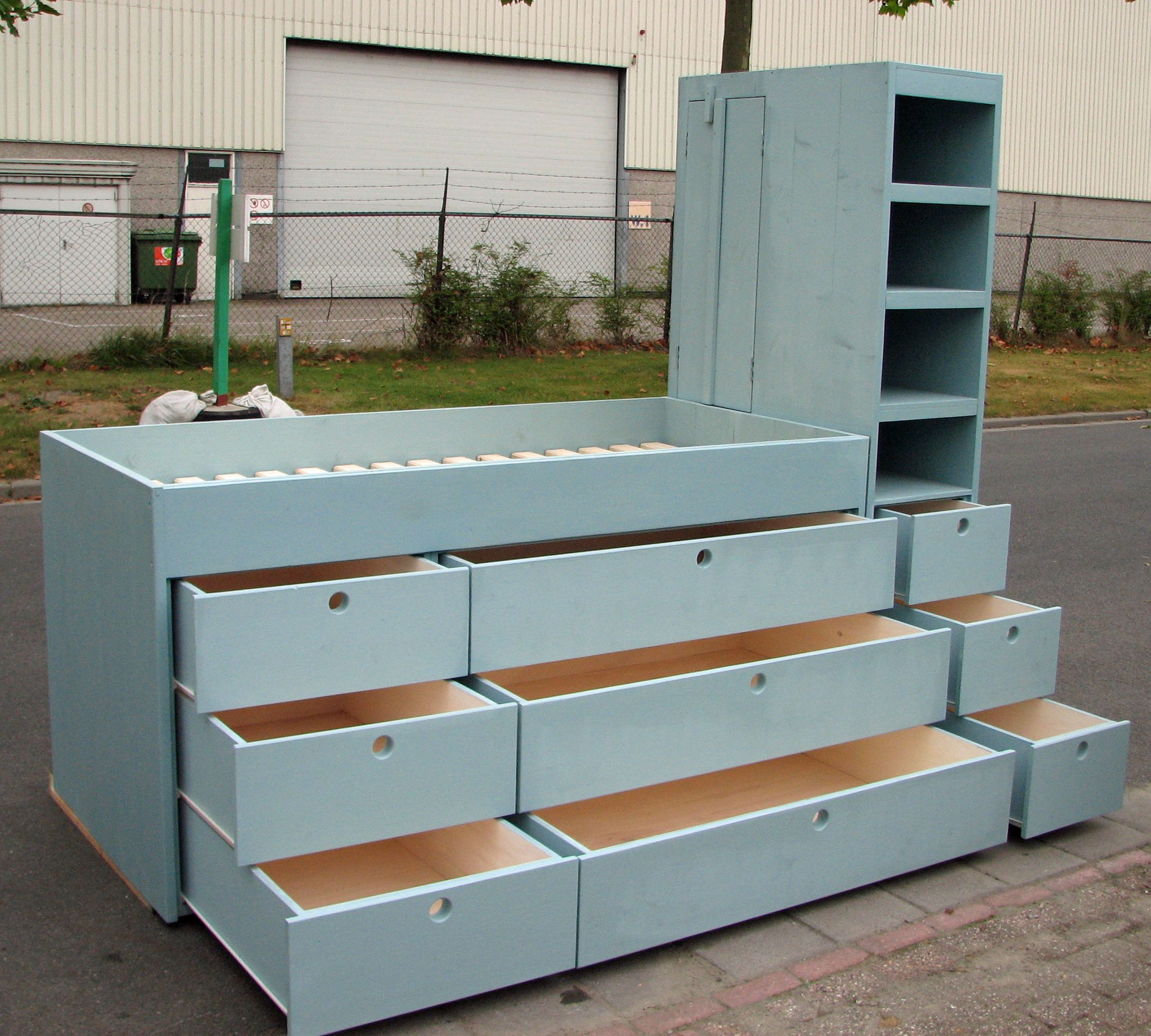 half hoogslaperbed met lade kast en boekenkast aan de zijkant de ideale kast voor een