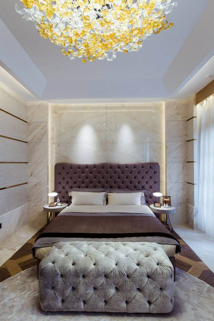 chambre moderne avec tête de lit capitonnée, bout de lit gris et ...