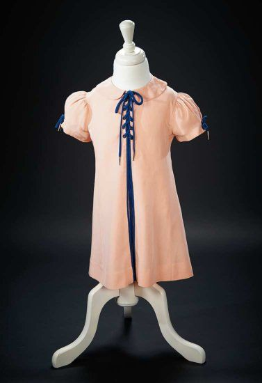 """Peach Silk Crepe Dress Worn by Shirley Temple in the 1936 Film """"Stowaway"""" Of peach silk crepe, the flare-sided front has hidden pleats at the center front and sides that allow fluid movement, Peter Pan collar, short puffed sleeves, grommets and blue silk lacing at the bodice and sleeve edges, and blue silk edging at the front pleats. Included is a vintage photograph of Shirley wearing the dress. The dress was worn by Ching-Ching (Shirley Temple) in the 1936 film """"Stowaway"""" Z"""