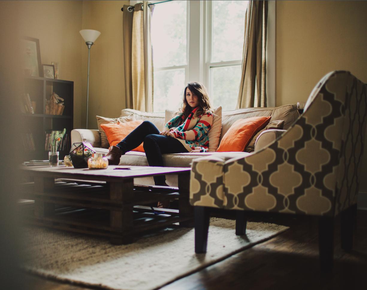 My living room. Orange neutral, geometric pattern slipper chair, repurposed wood coffee table. Photo by Ariel Renae