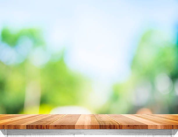 Empty Brown Wood Table Top With Sun And Blur Tree