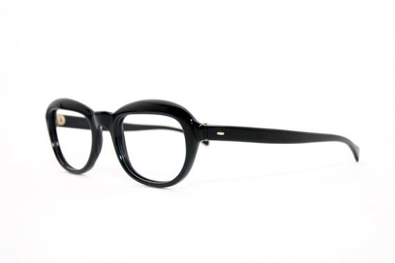 Original 60's new old stock eyeglasses with oval lens holders and a deep black colour. The model is called Tatiana and was made in Italy.FREE SHIPPING WORLDWIDENEW OLD STOCK in great condition, slight patina on the hinges. The quality is proper with strong hinges.Women's glasses for her, for the small to medium sized head. Dimensions:46mm for the lens width, 33mm for the heightNose bridge: 20mmTotal width: appr. 129mmTemple: appr. 130mm, and can be bent to any size within the small to medium ran