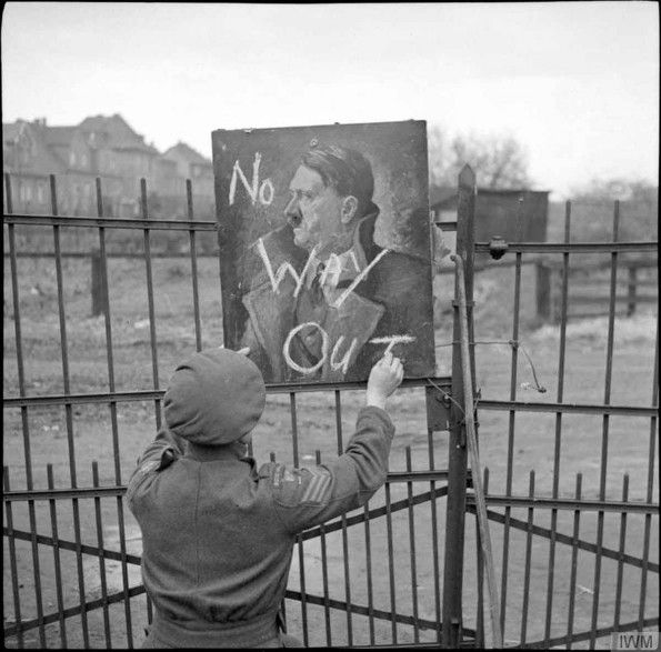 'No Way Out'. Sgt J D Eilbeck uses a portrait of Adolf Hitler to make a 'no exit' sign at 156th Brigade HQ, 3 - 4 April 1945.