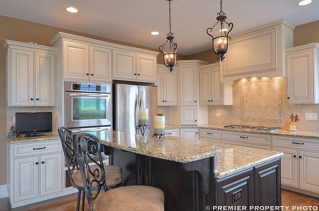 White Kitchen Dark Island glazed white cabinets, dark island, travertine backsplash, lantern