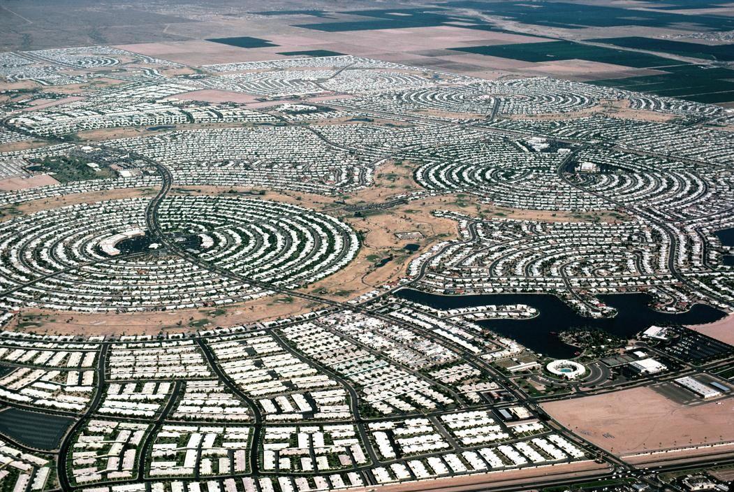 Sun City, Arizona. La planta es demencial. La vista de las calles lo es aún más. Se duplicó con Sun City Westhace unos cuantos años.  Aerial view over Sun City showing the clever layout that allows everyone to be near the centre. There are about 46,000 residents. 1992.