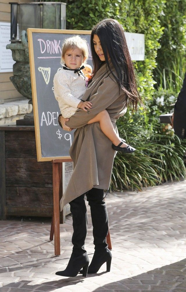 Kourtney Kardashian wears a neutral wrap dress with thigh-high suede boots