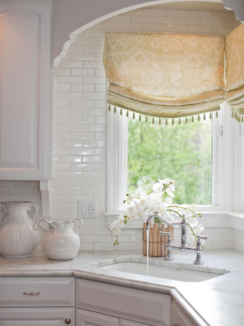 A corner sink takes center stage in this white traditional kitchen ...
