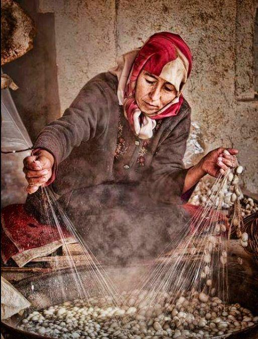 Gravura:mulher tirando os fios dos casulos.