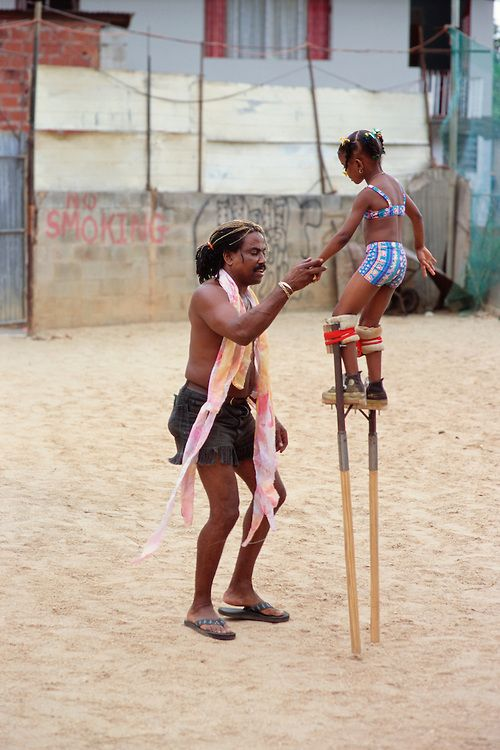"Trinidad and Tobago ""MOKO JUMBIES: The Dancing Spirits of Trinidad"".(Dragon Glen de Souza teaches five-year-old N'Neka Pompey on the first day she graduated from three-foot to four-and-a-half-foot stilts. The stilts can weigh from 8 to 10 pounds each, for the 3-foot stilts, and as much as 25 pounds or more for each 6-foot stilt.).A photo essay about a stilt walking school in Cocorite, Trinidad..Dragon Glen de Souza founded the Keylemanjahro School of Art & Culture in 1986. The main purpose…"