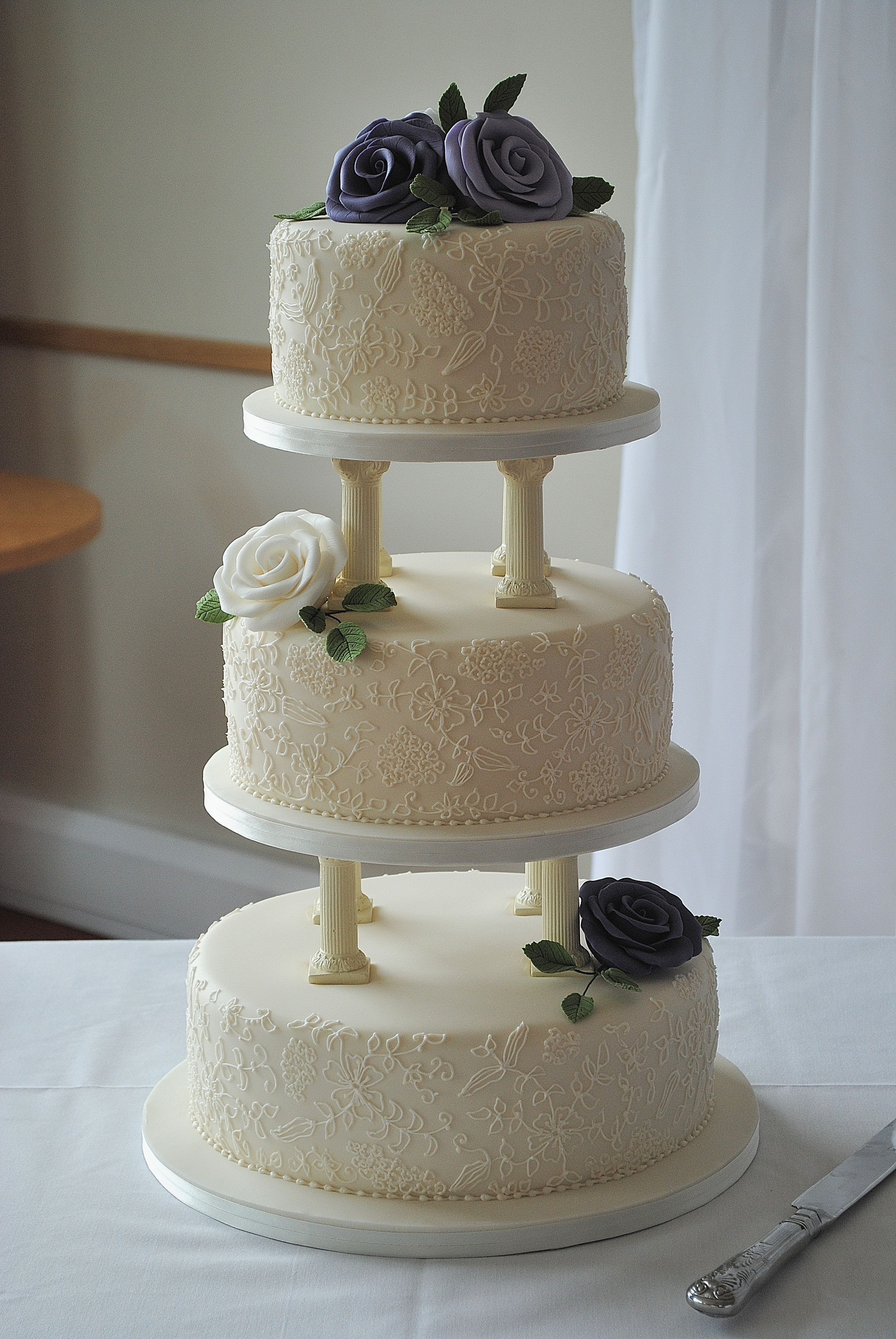 3 tier wedding cake with pillars hand piped lace and hand