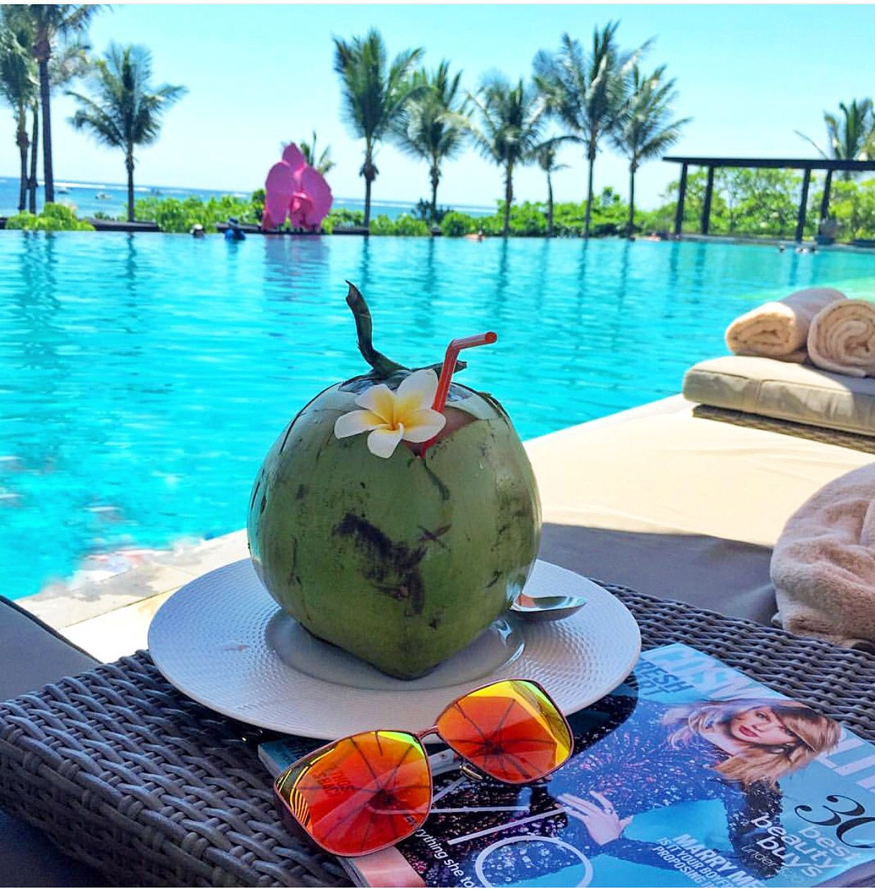 Sipping fresh young coconuts poolside at Fairmont Sanur