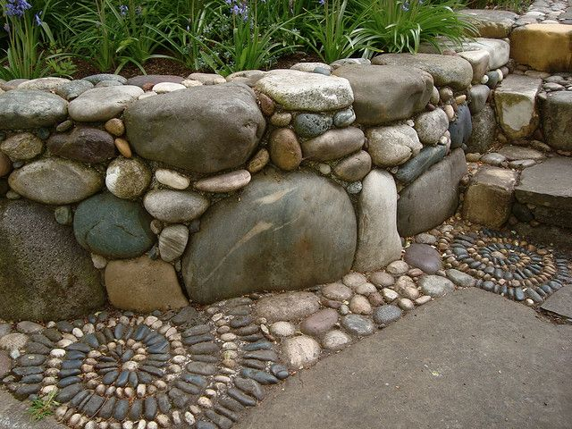 River Rock Retaining Wall With Spirals Rock Retaining Wall Outdoor Gardens Garden Design