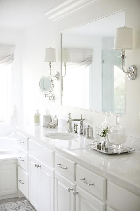 A White Framed Vanity Mirror Is Lit By Two Polished Nickel Sconces - Sconces mounted on bathroom mirror