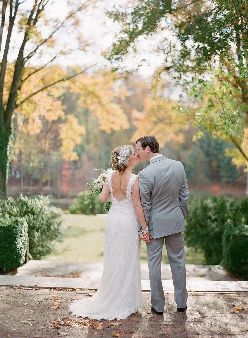 kissing newlyweds under fall leaves at verulam farm wedding