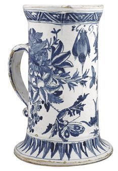 A LONDON DELFT DATED BLUE AND WHITE CYLINDRICAL MUG 1669 The strap handle with blue scrolls and with scroll terminal, painted with birds in flight, butterflies and a grasshopper among groups of flowers and foliage, the spreading upper rim with trefoils within zig-zag ornament, the spreading foot with stiff leaves
