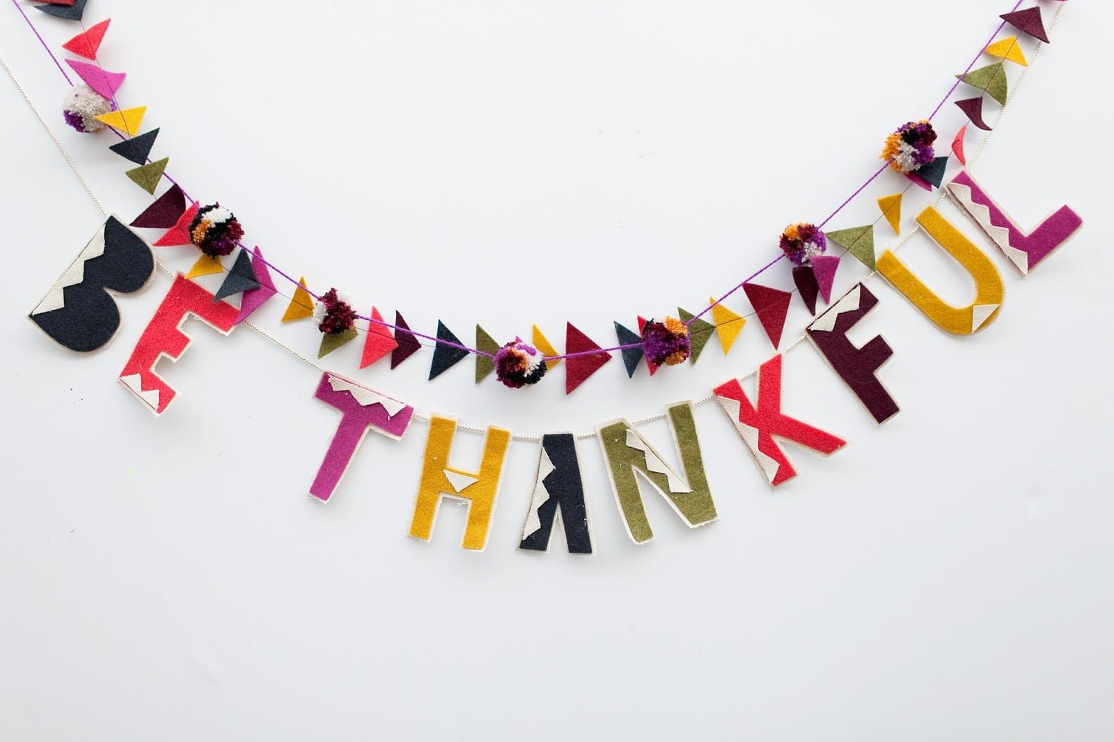 The key to making this Thanksgiving garland by Tell Love & Party is cutting out letters slowly and carefully—or just stick with the pompoms if you're hopeless at cutting neatly!