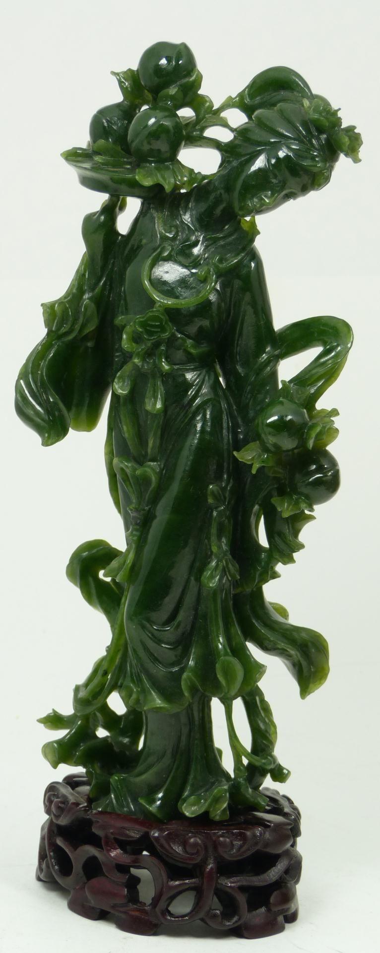 Carved jade figure depicting guan yin holding a platter