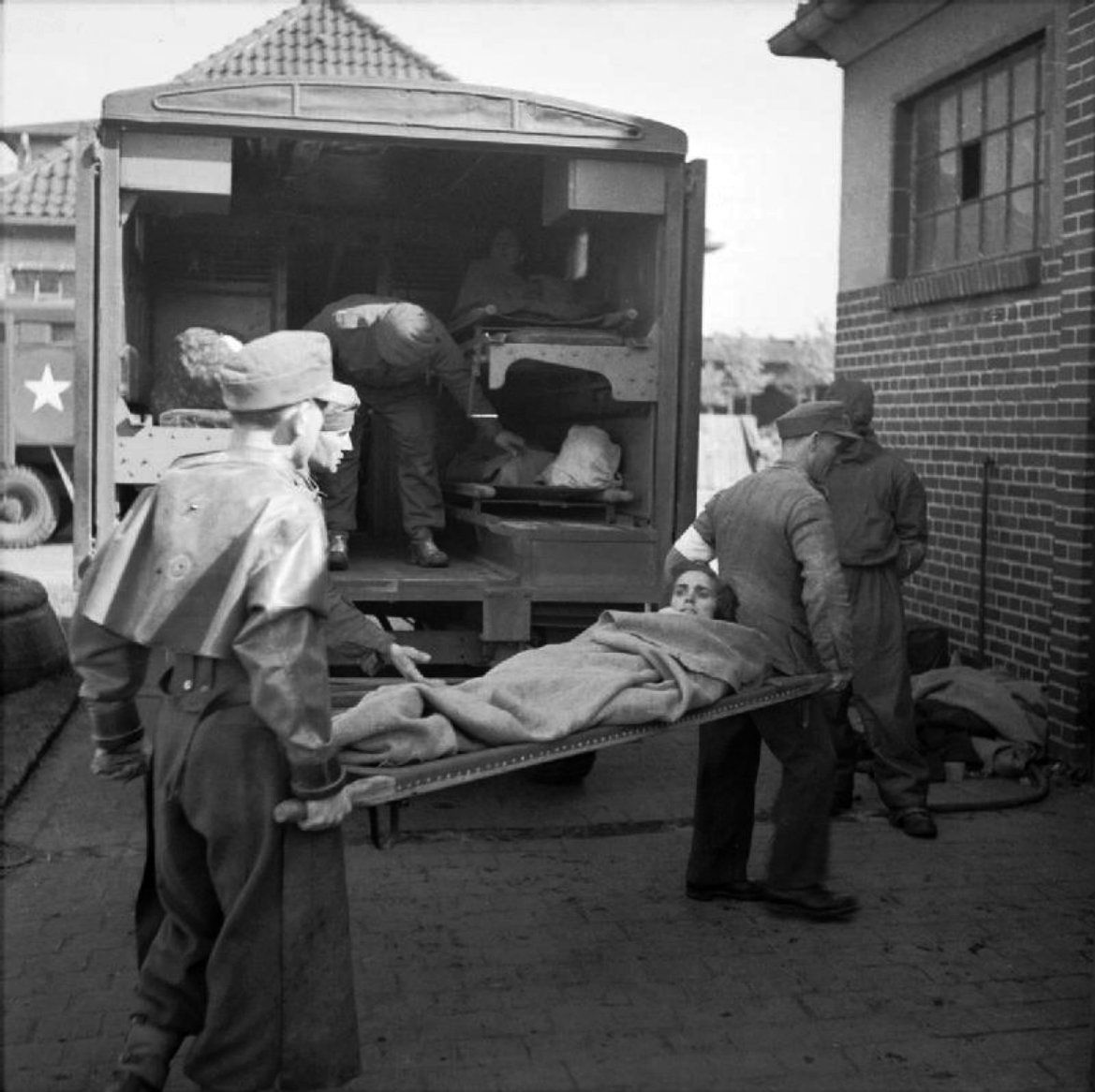 "German POWs and British Royal Army Medical Corps orderlies unload ill former inmates at the cleansing station at Hohne Barracks, which acquired the nickname the ""Human Laundry"" following the British liberation of Bergen-Belsen concentration camp. Stable Blocks were converted into improvised decontamination facilities. Here, former prisoners would arrive, be shaved, washed and deloused prior to being moved into the newly established hospitals within Bergen-Belsen Barracks. Bergen-Belsen…"