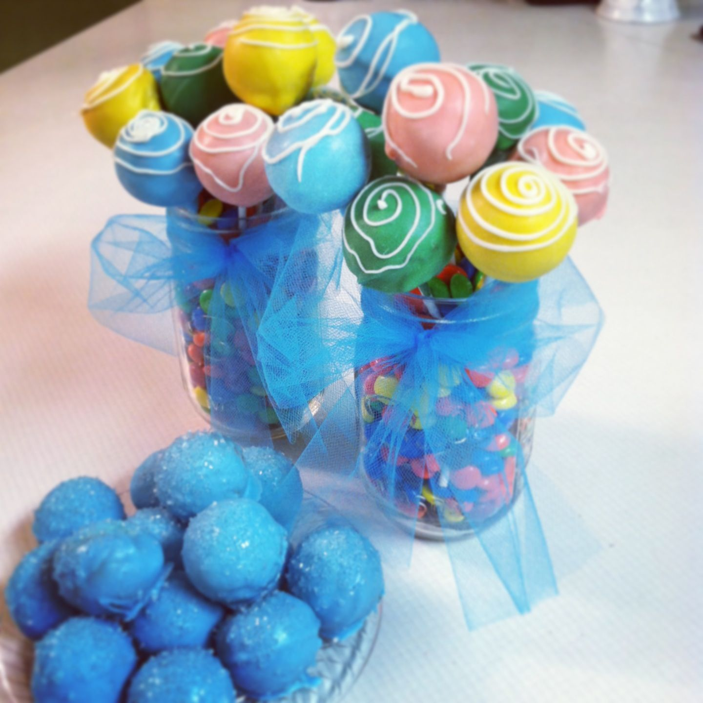 Cake pop bouquet presentation! Fill a mason jar with candy, stick in multi colored cake pops, and add a bow! So easy! #cakepopbouquet