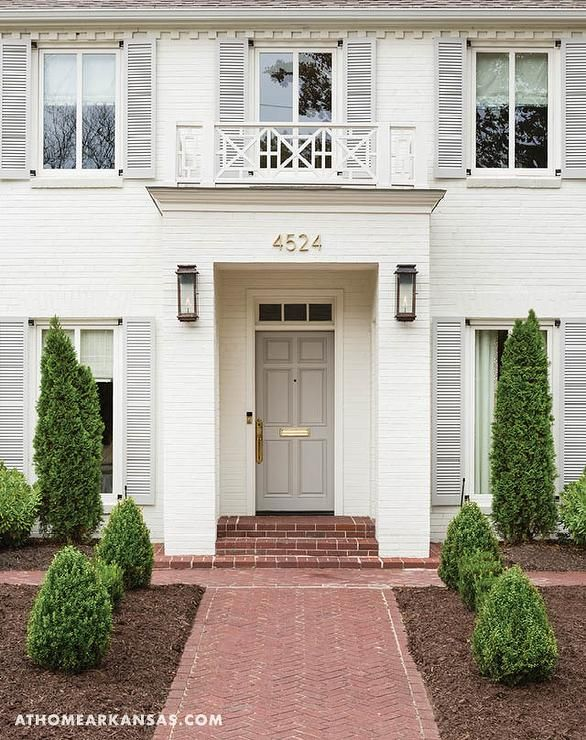 A Brick Pathway Leads To A White Brick Home Accented With Gray