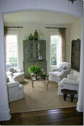 I love the airy and light feel in this room. Sisal rug, small table ...