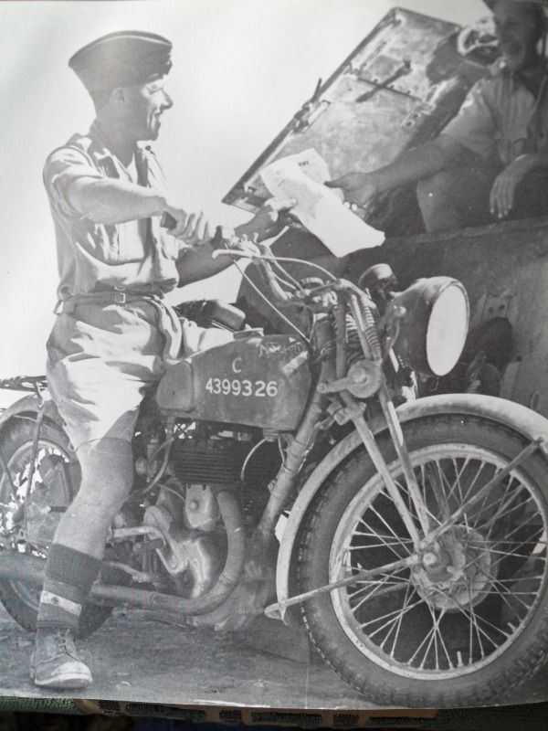 A 16h Norton rider delivers the 8th army news to an armoured car in the desert