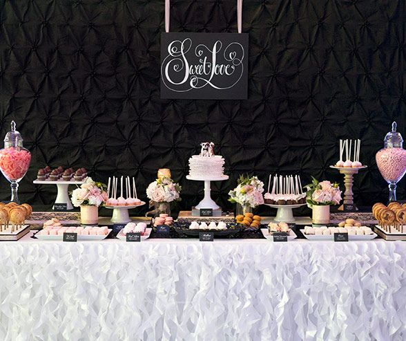 A wedding dessert table stands out against a dark textured fabric wall.